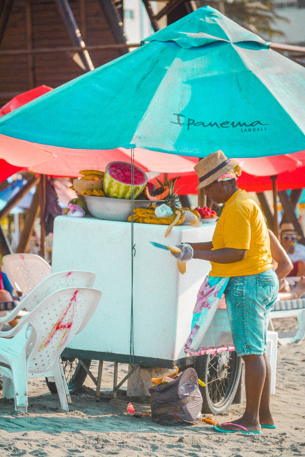 woman in yellow tee shirt standing by the fruit stall