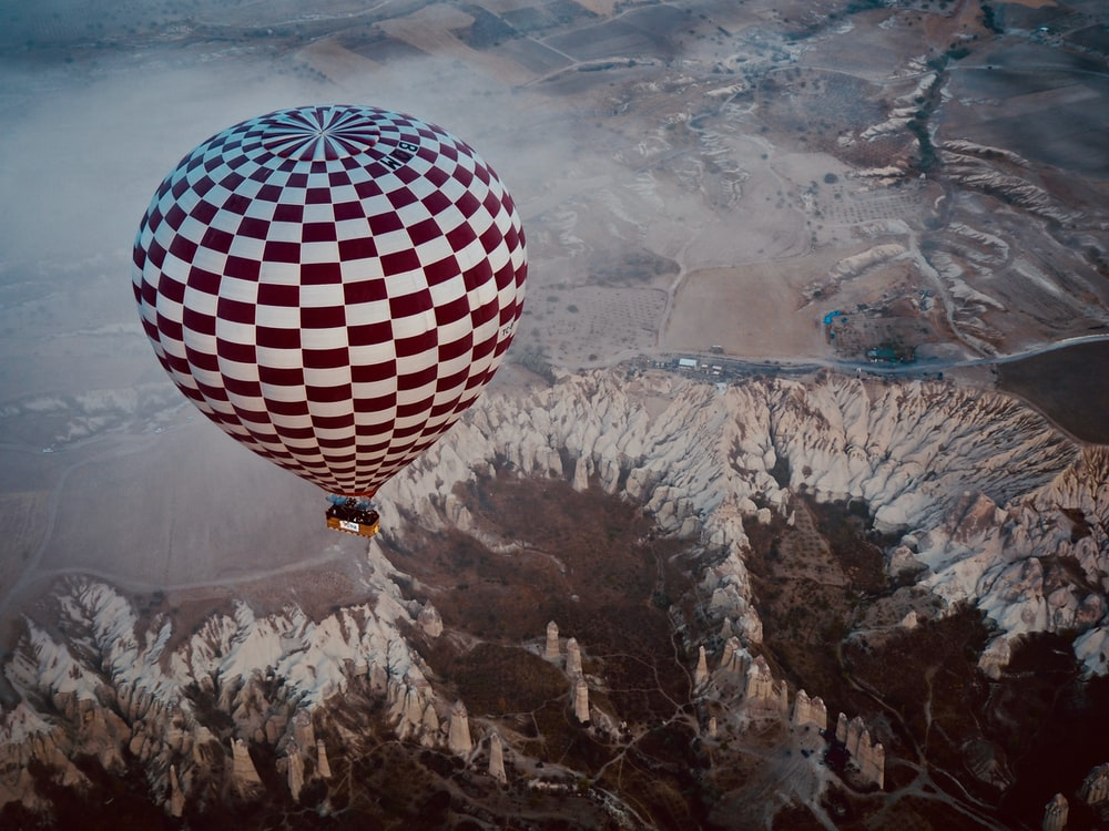 hot air balloon hovering over mountainous terrain during daytime
