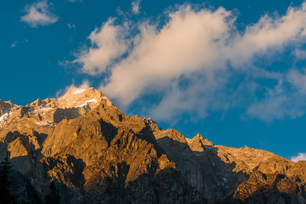 brown rocky mountain under white and blue cloudy sky