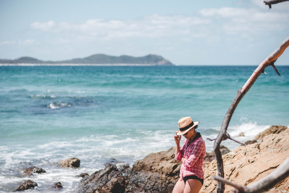 woman standing on rock beside ocean at daytime