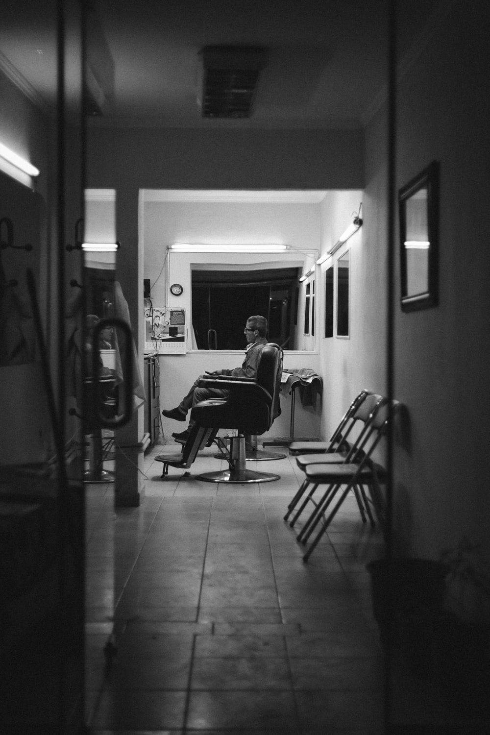 grayscale photo of man sitting on chair