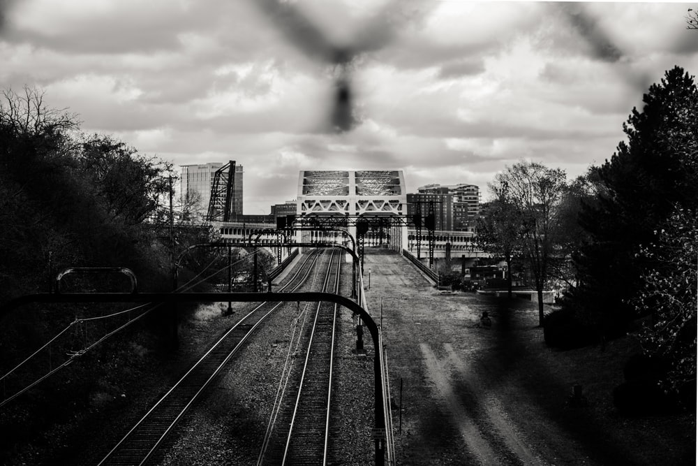 grayscale photo of train track during daytime