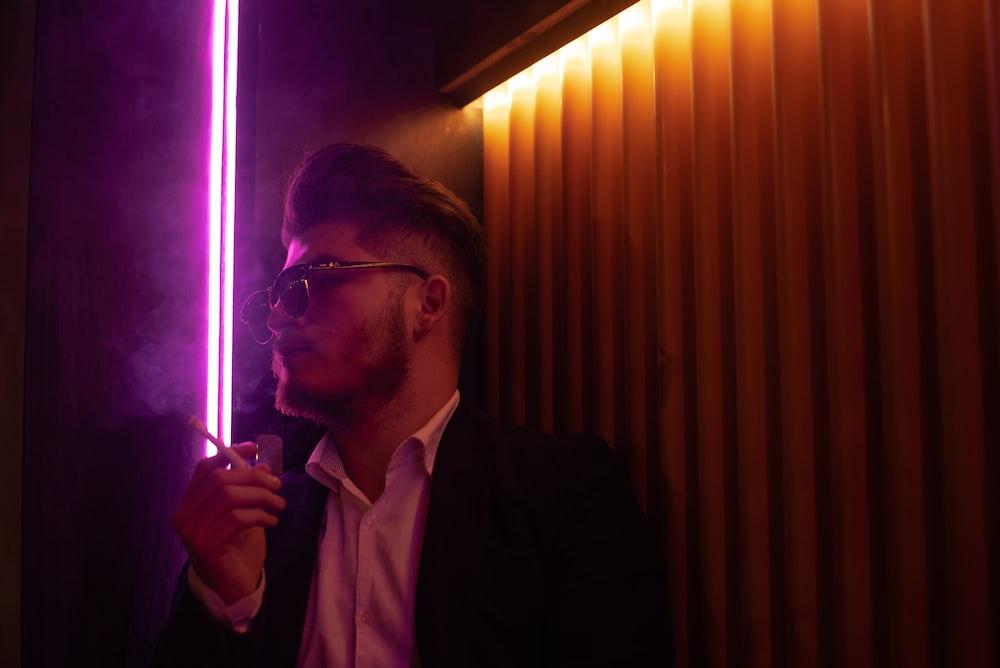 man in black suit jacket smoking cigarette