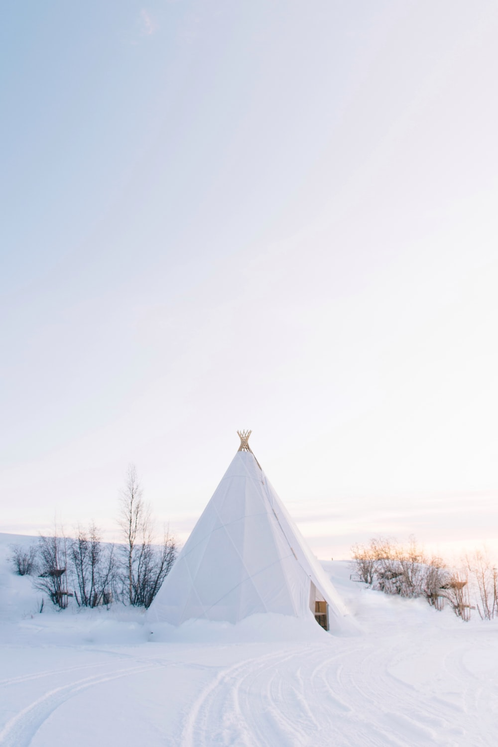 white tipi tent covered with snow