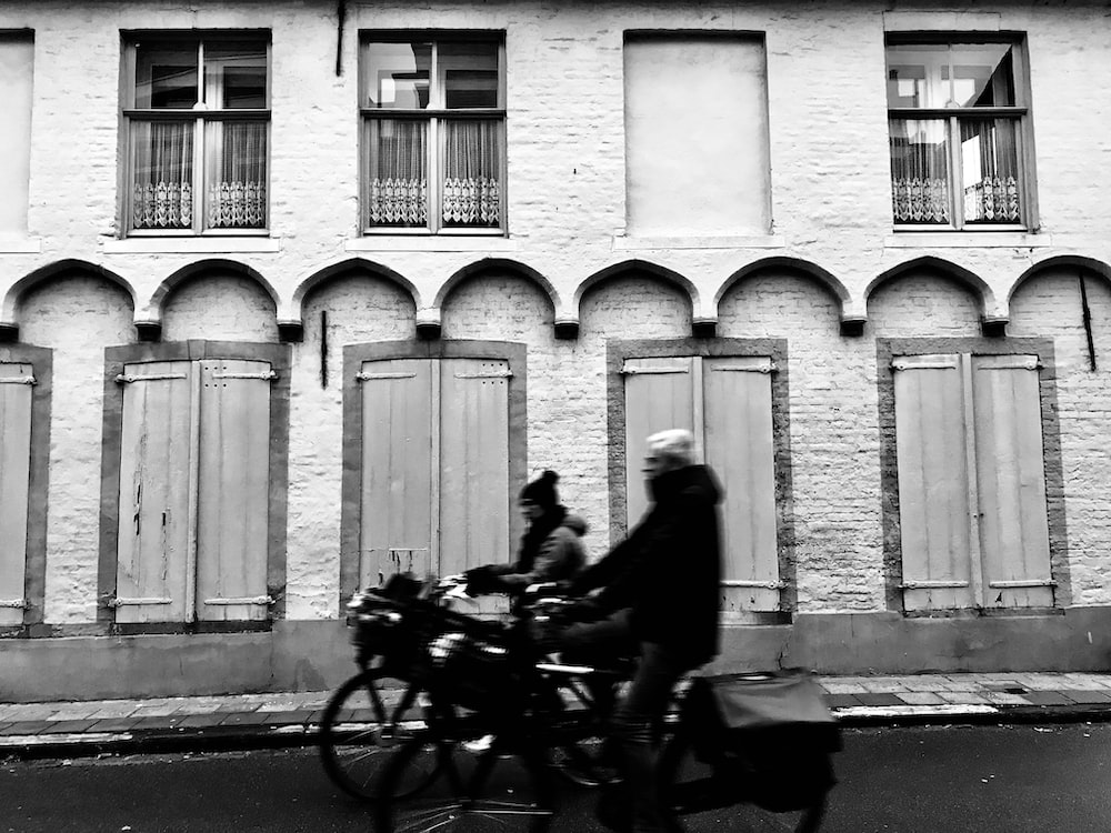 grayscale photography of two persons riding bicycle