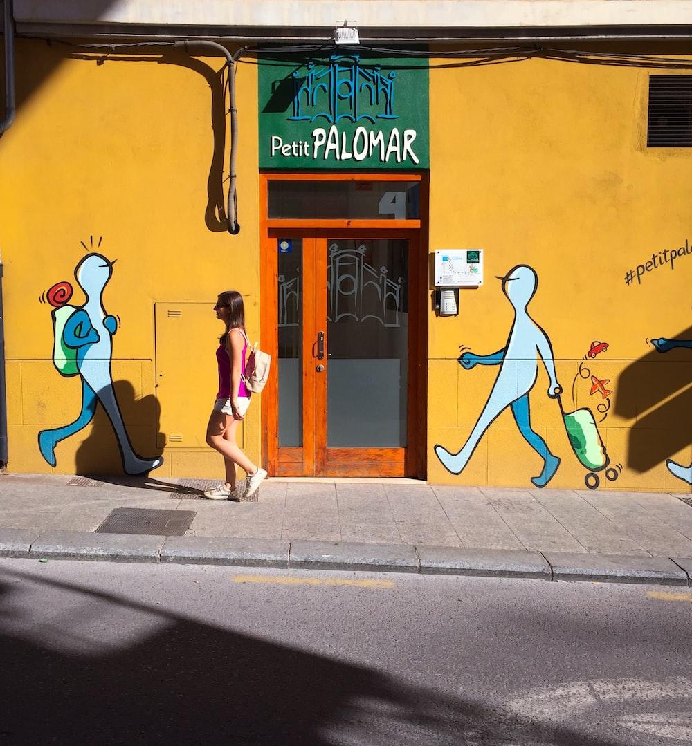 woman walking on sidewalk near Petit Palomar building