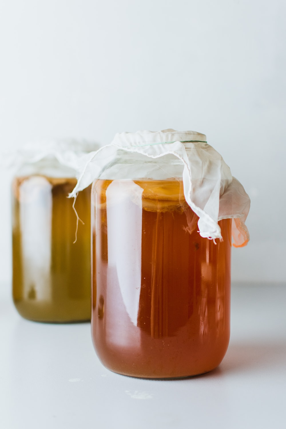 two mason jars filled with liquid on white surface