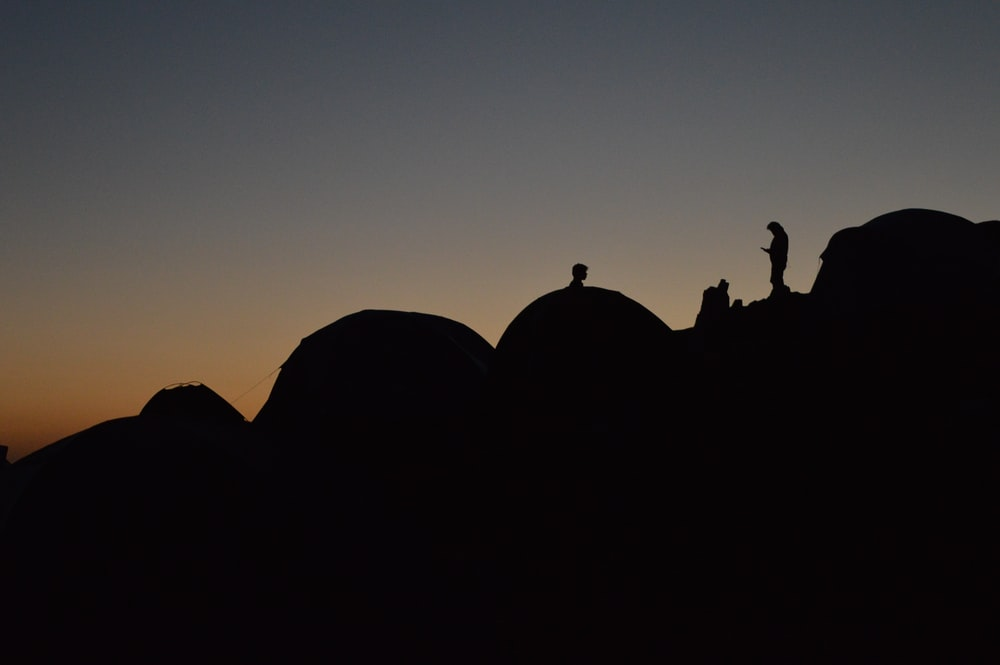 silhouette of people on hills during sunset