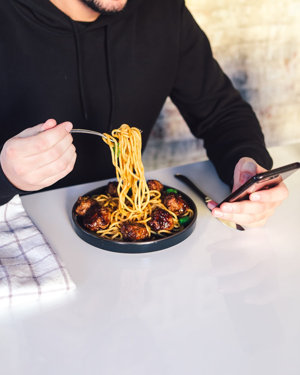man eating cooked noodle while using phone