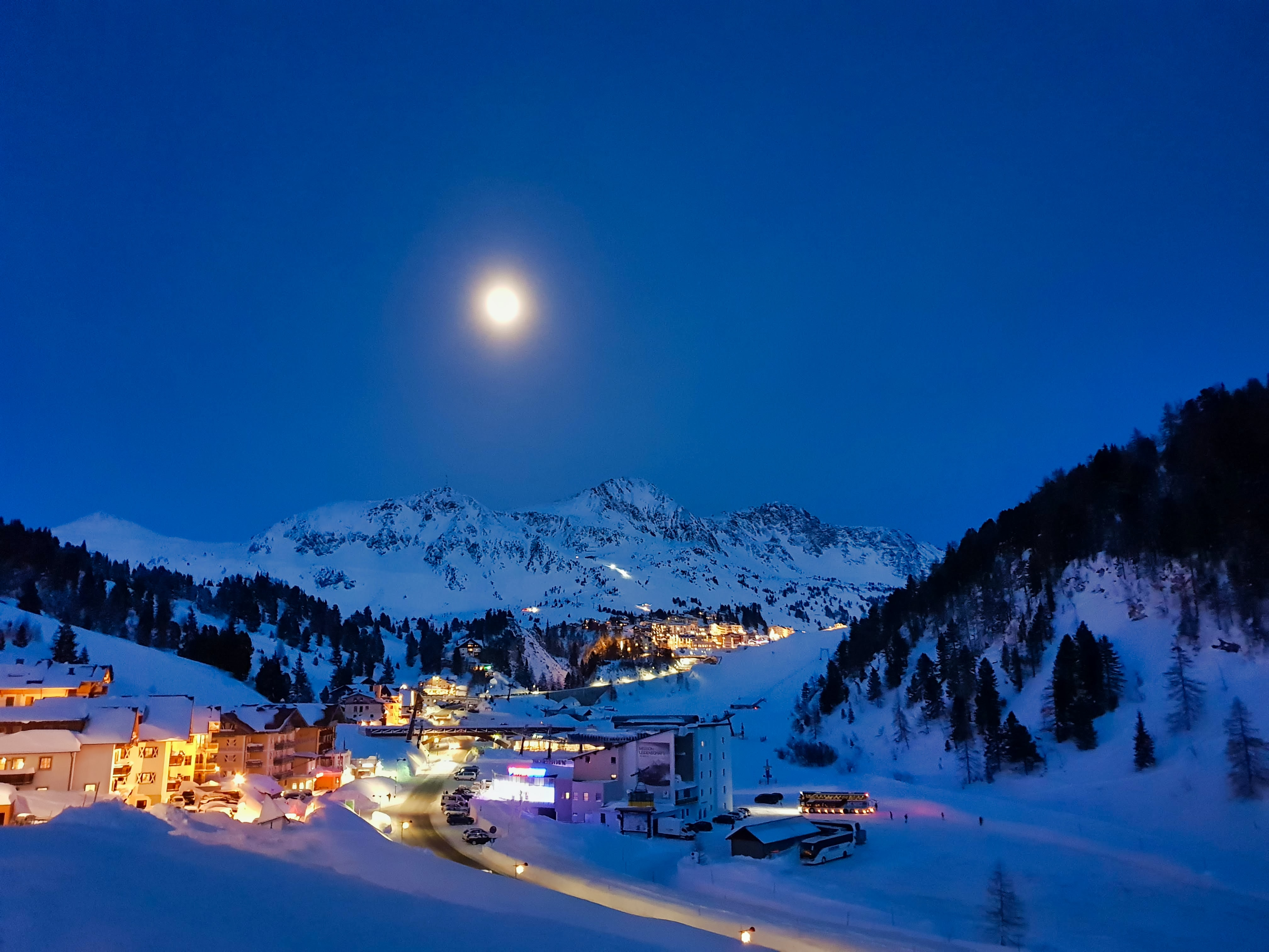 lighted buildings and houses with snow covered field during night time
