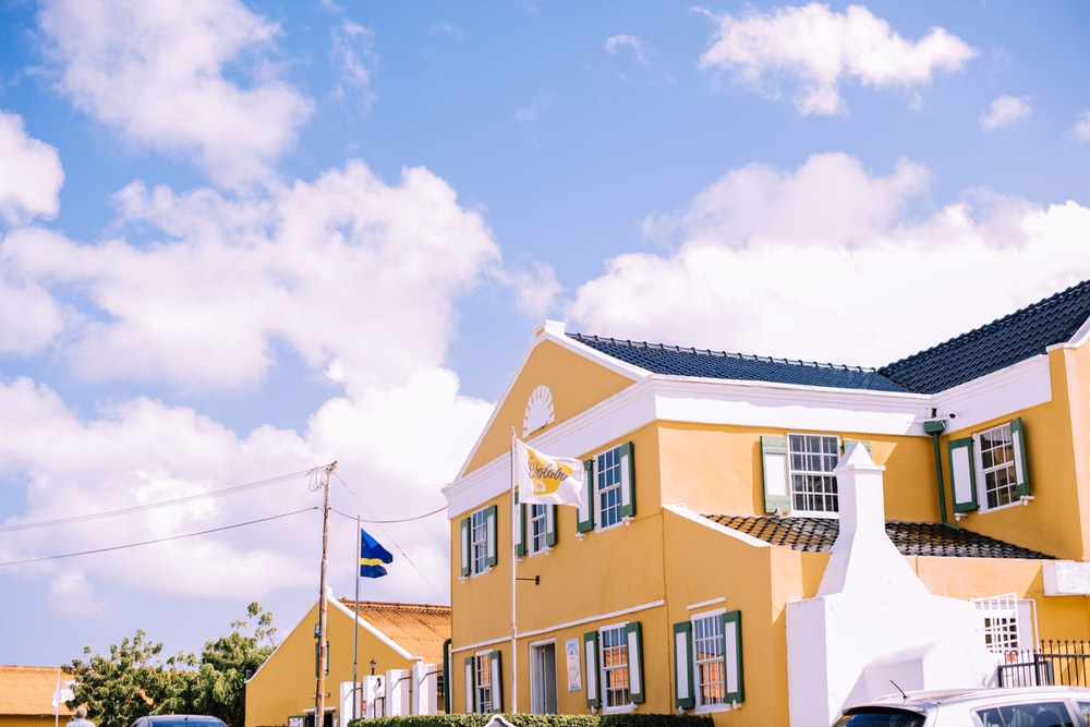 yellow and white house under blue and white sky