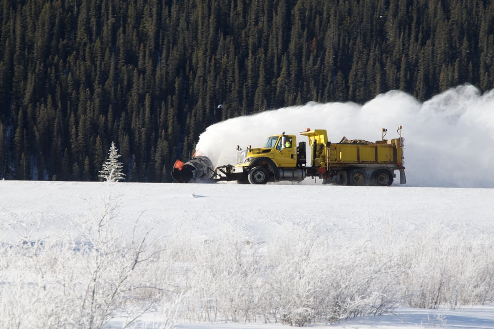 yellow dump truck on snow field during daytime