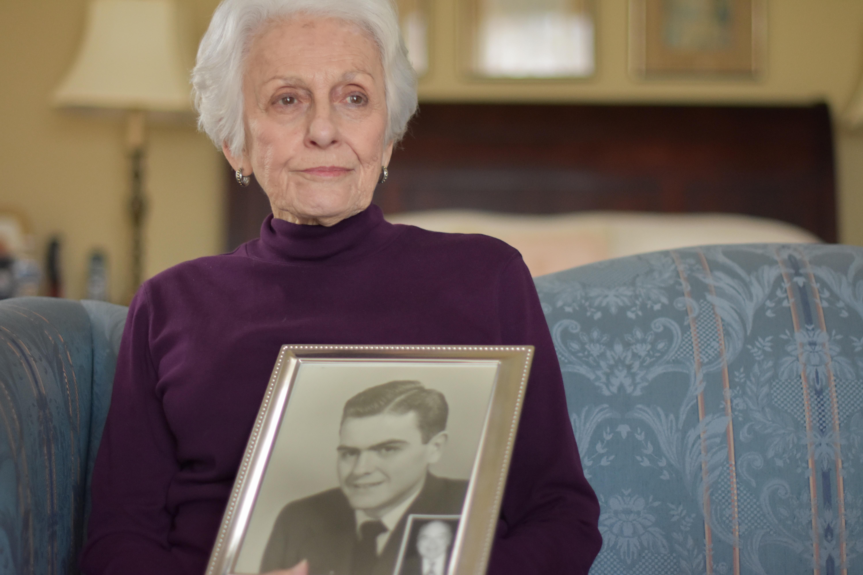 woman holding portrait photo of man