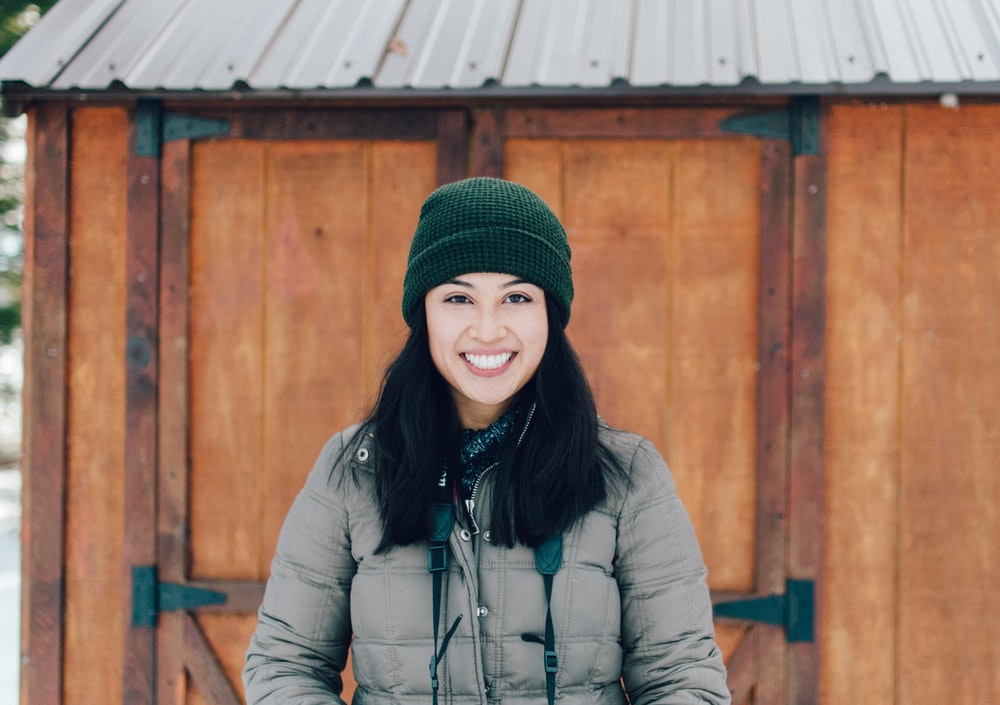 smiling woman in brown jacket standing beside brown wooden shed