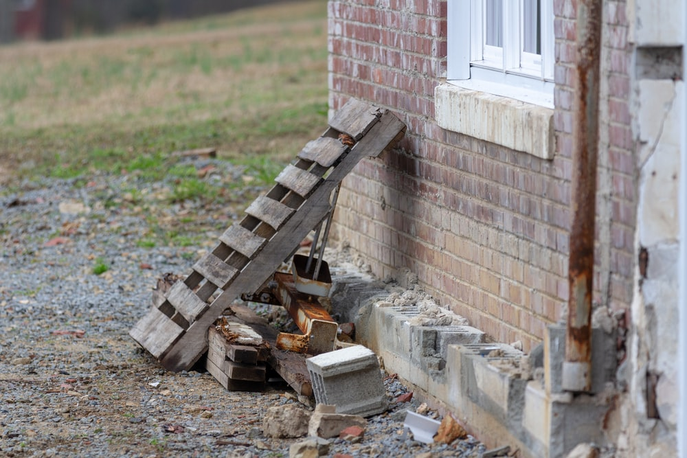 brown wooden ladder beside brick wall