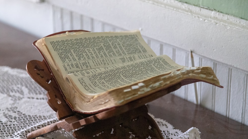 opened Bible on brown wooden stand