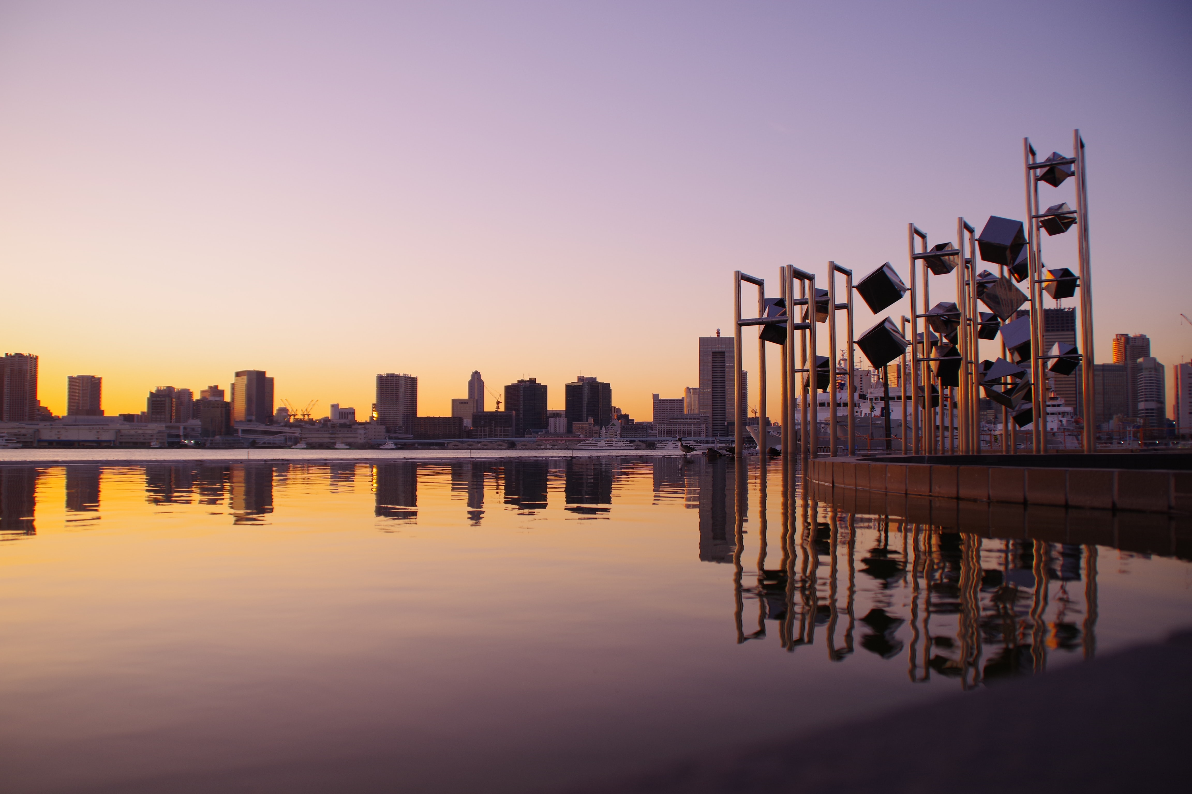 panoramic photography of buildings and towers reflecting on water during sunset