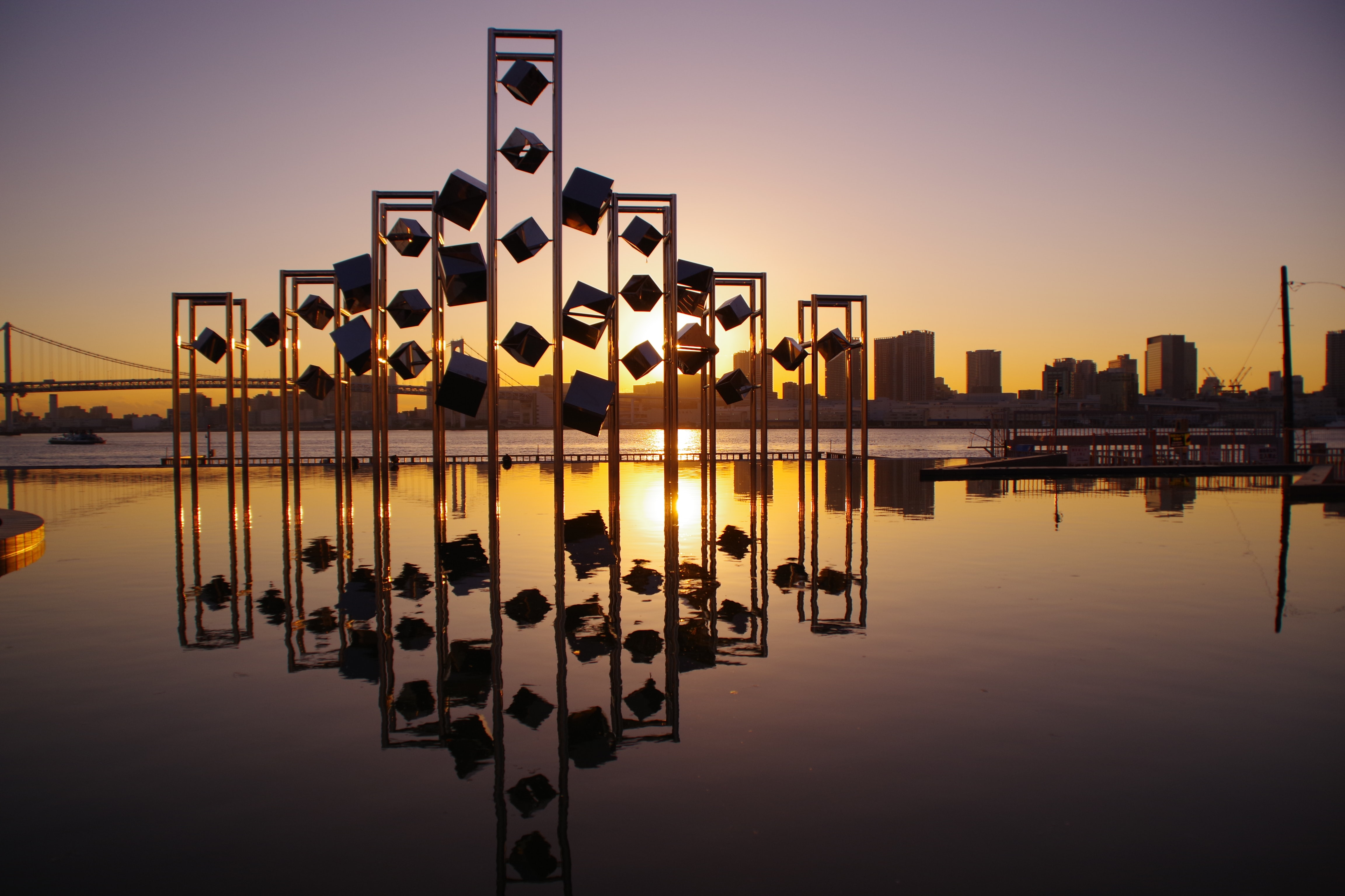 panoramic photography of buildings and towers reflecting on body of water during sunset