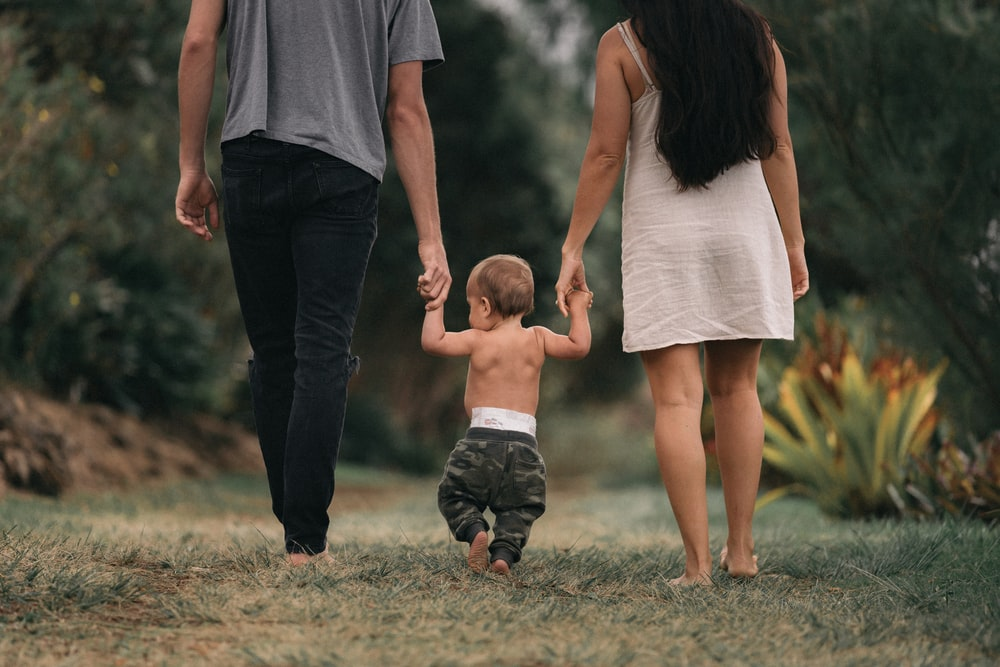 couple walking barefoot with a child at the garden