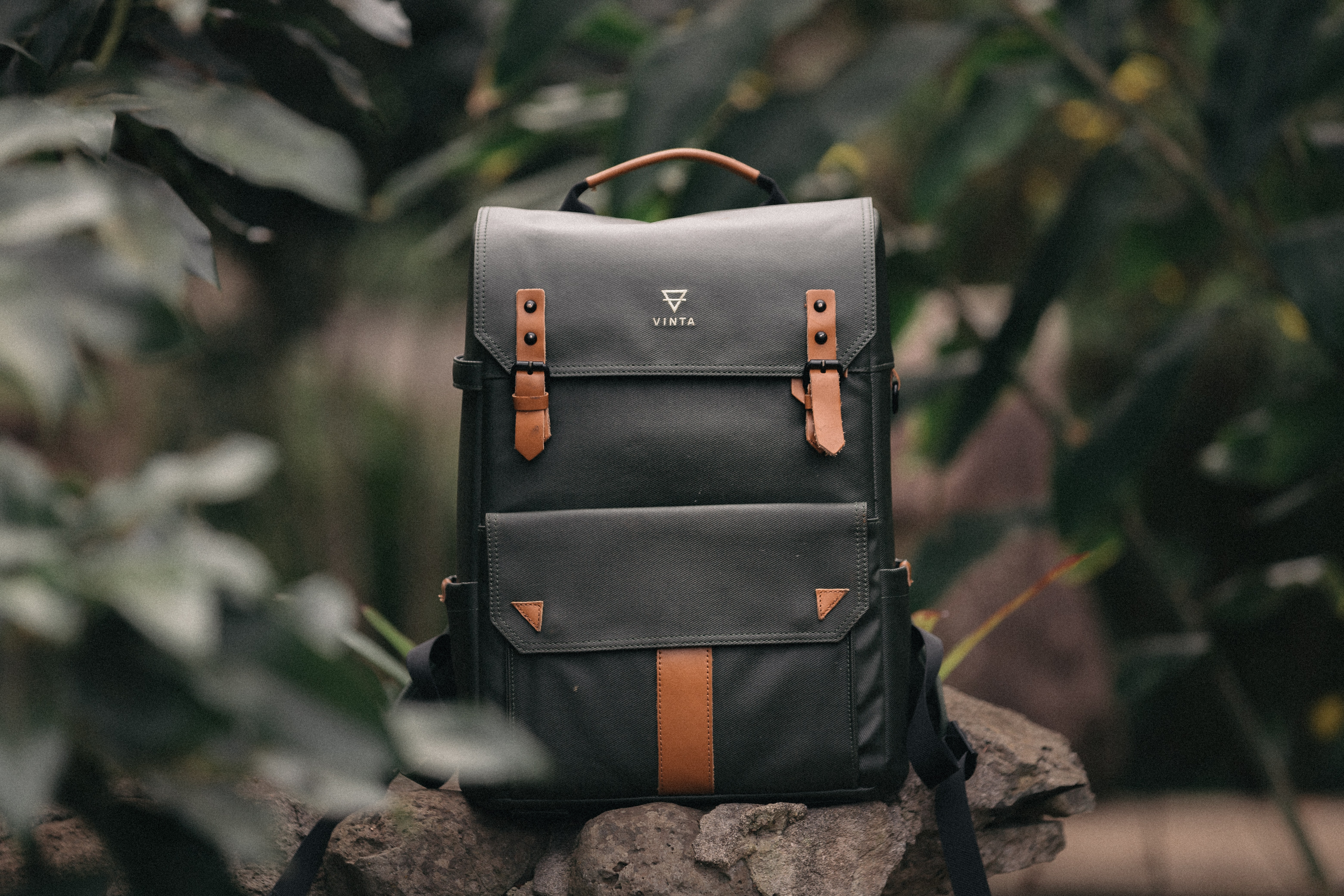 selective focus photography of black and brown leather backpack on rock