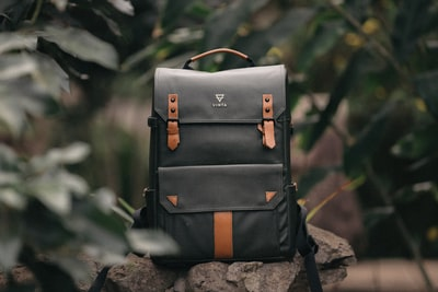 selective focus photography of black and brown leather backpack on rock product teams background