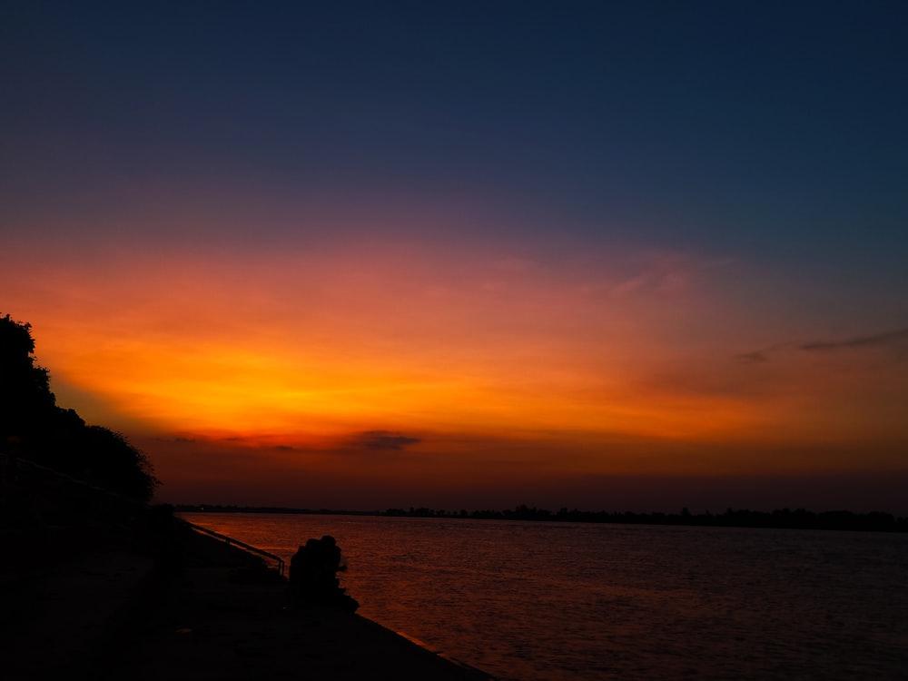 silhouette of field under orange sky