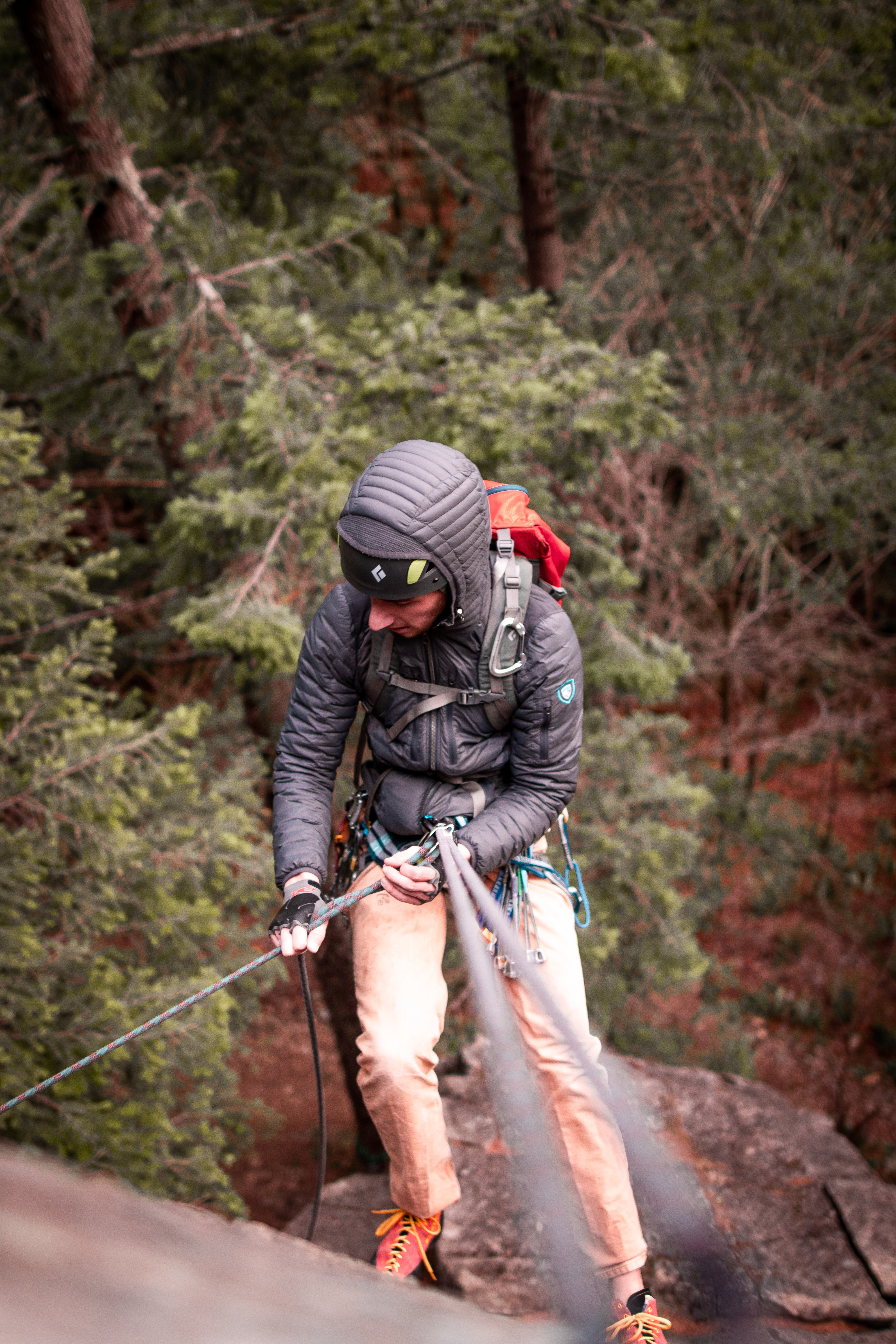person in gray jacket climbing hills