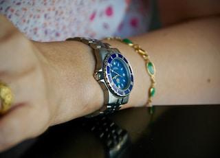 person wearing round blue analog watch