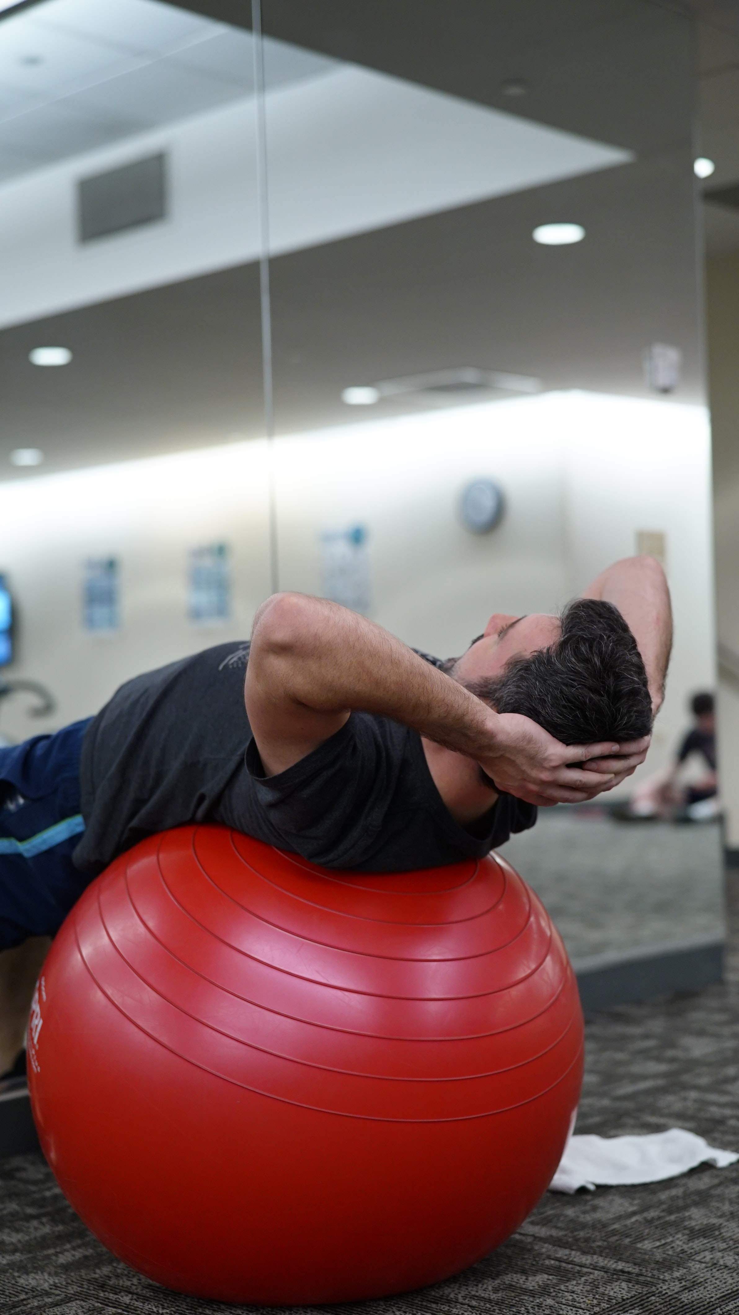 man lying on red stability ball