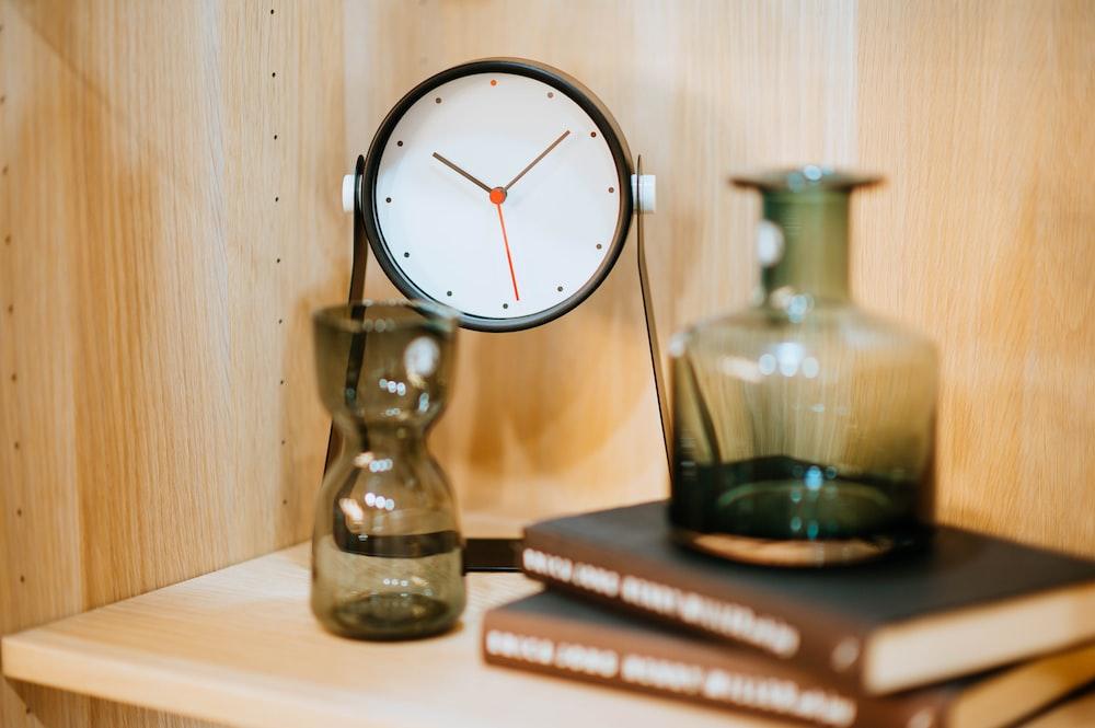 desk clock near vase on pile of books
