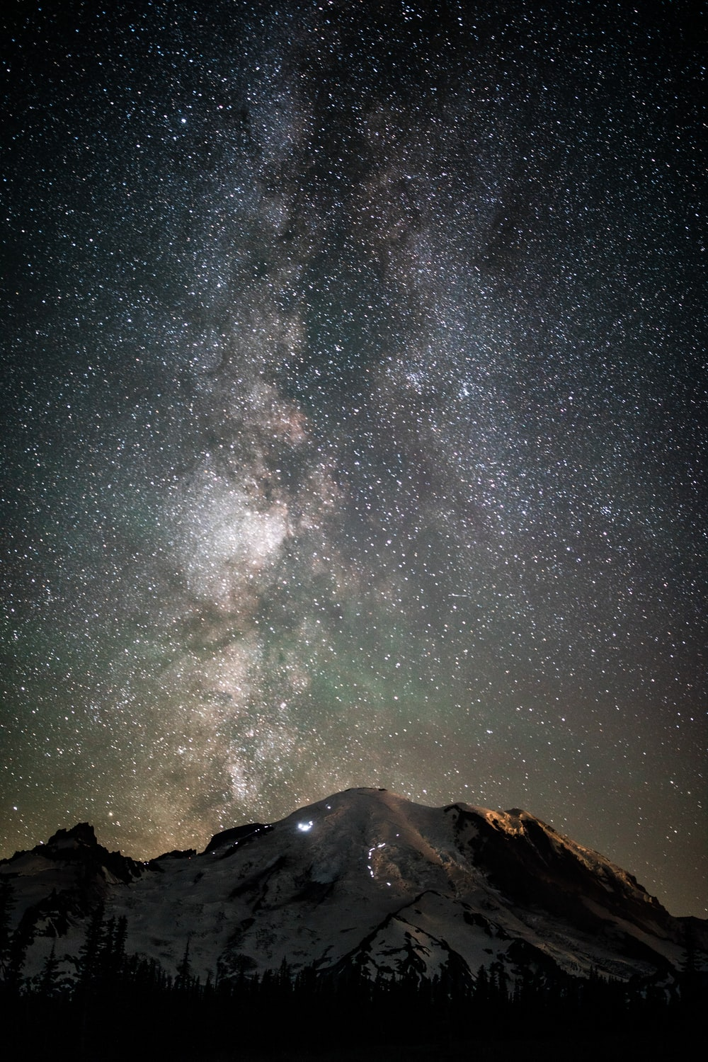snow covered mountain under stars during night time