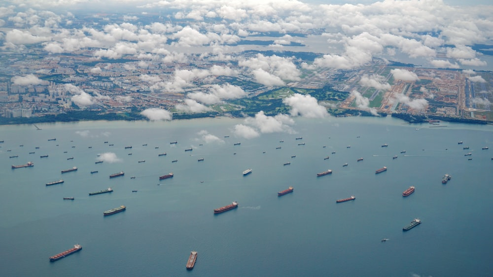 aerial photography of ships on calm sea under dramatic clouds during daytime