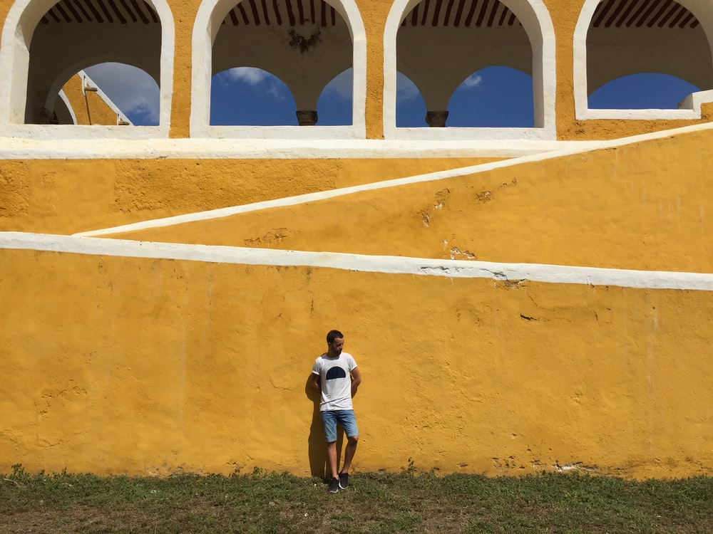 man in white shirt leaning on yellow concrete wall during daytime