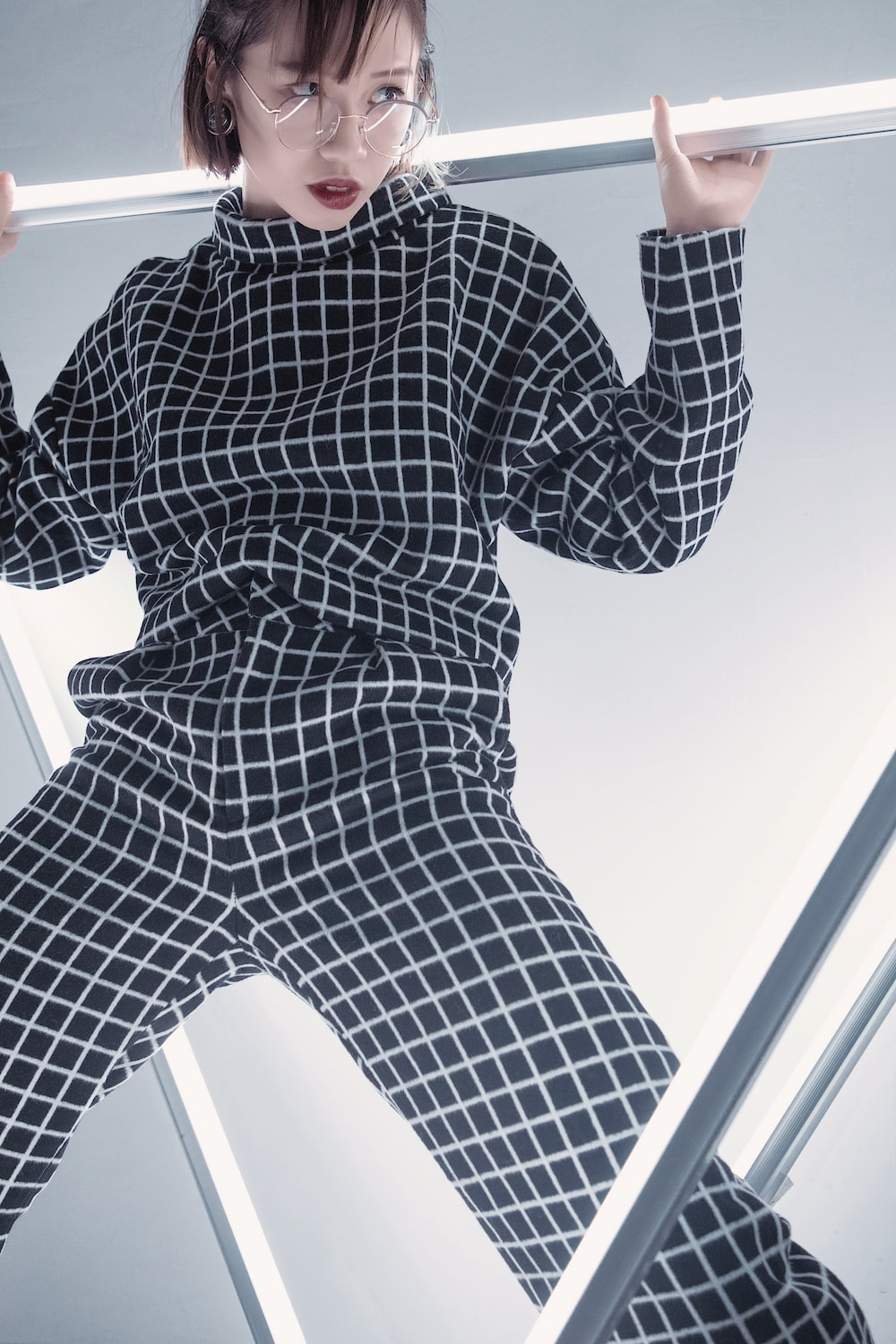 woman in gray and white checked overalls standing on metal bars