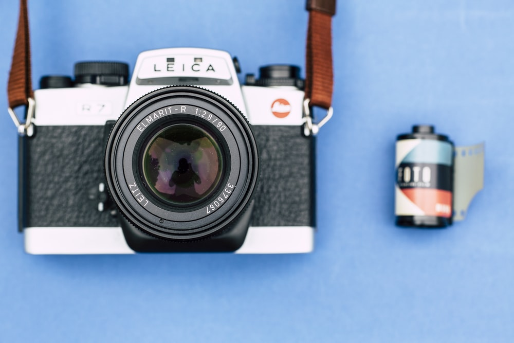black and gray Leica camera beside film on blue surface