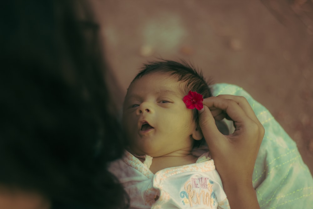 woman putting flower on baby's ear photo