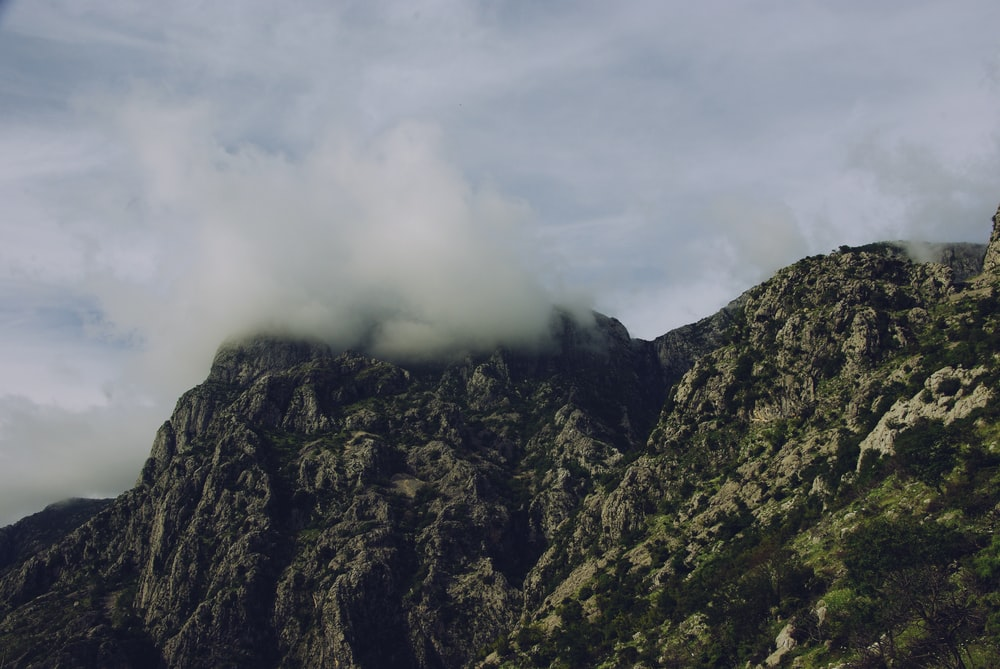high-angle photography of mountain under white clouds