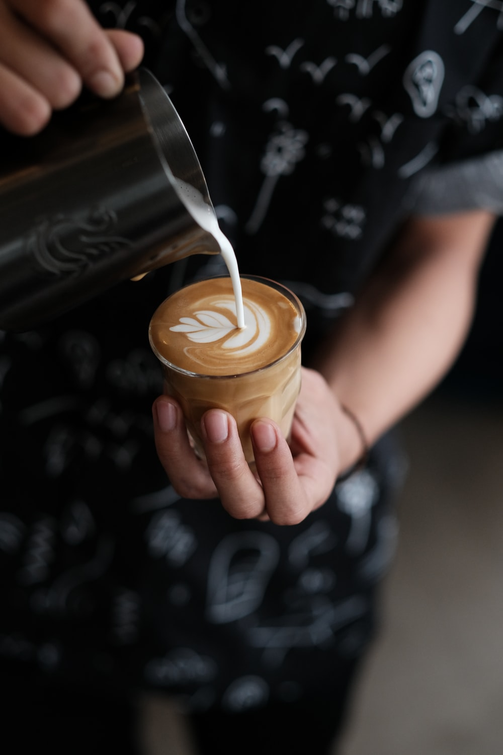 person holding cup of coffee pouring milk