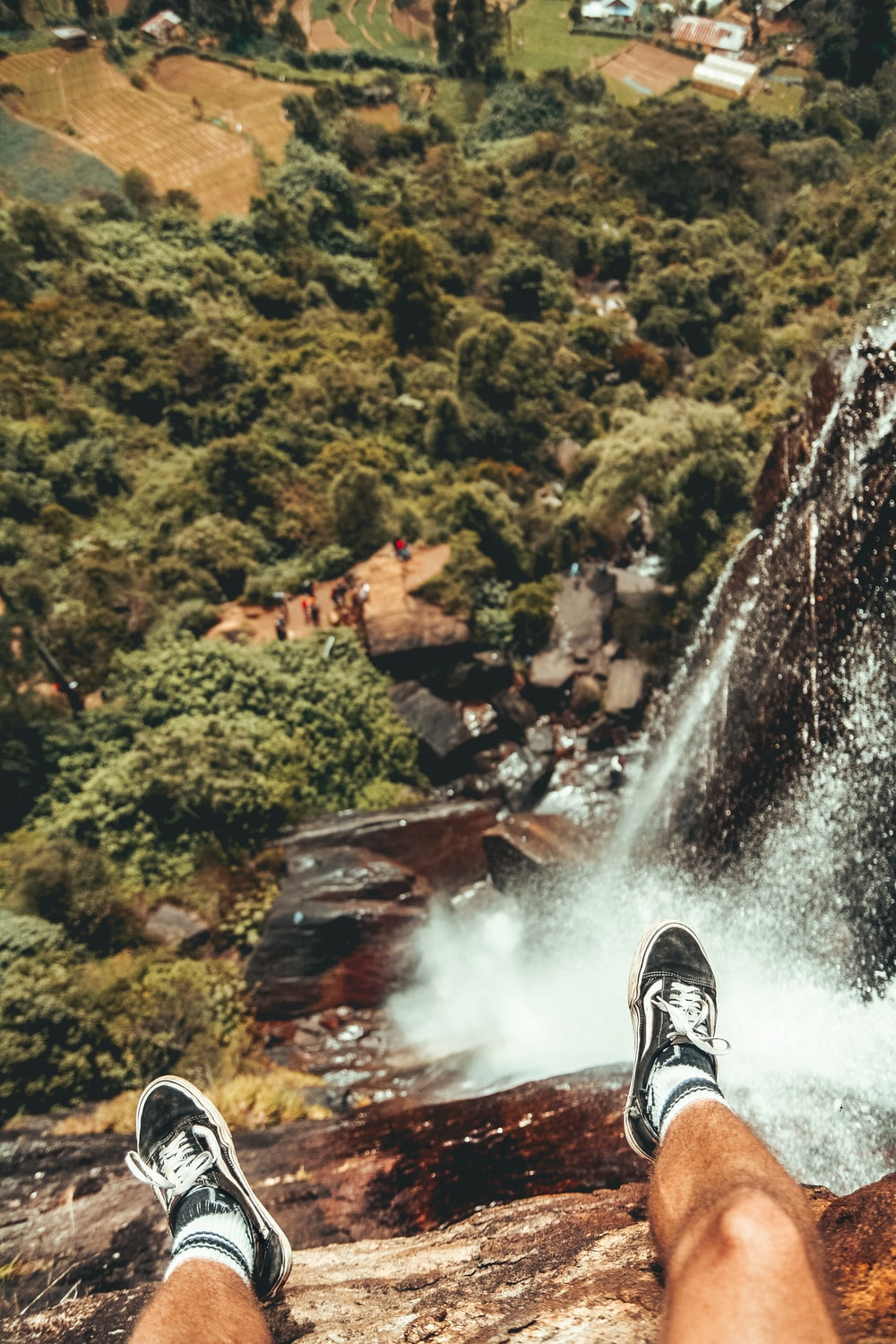 man sitting on edge of waterfalls