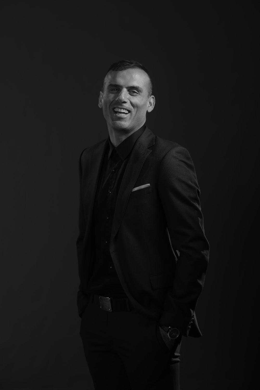grayscale photography of man wearing black tuxedo
