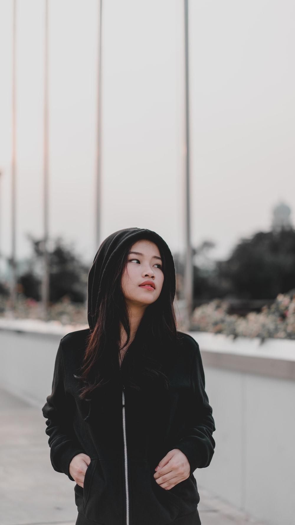 woman wearing black hooded jacket standing outdoor