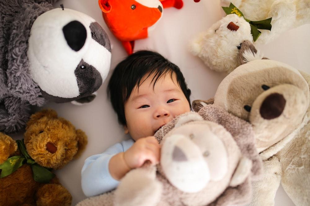 baby playing brown bear plush toys