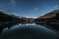 reflective photography of mountain alps on body of water