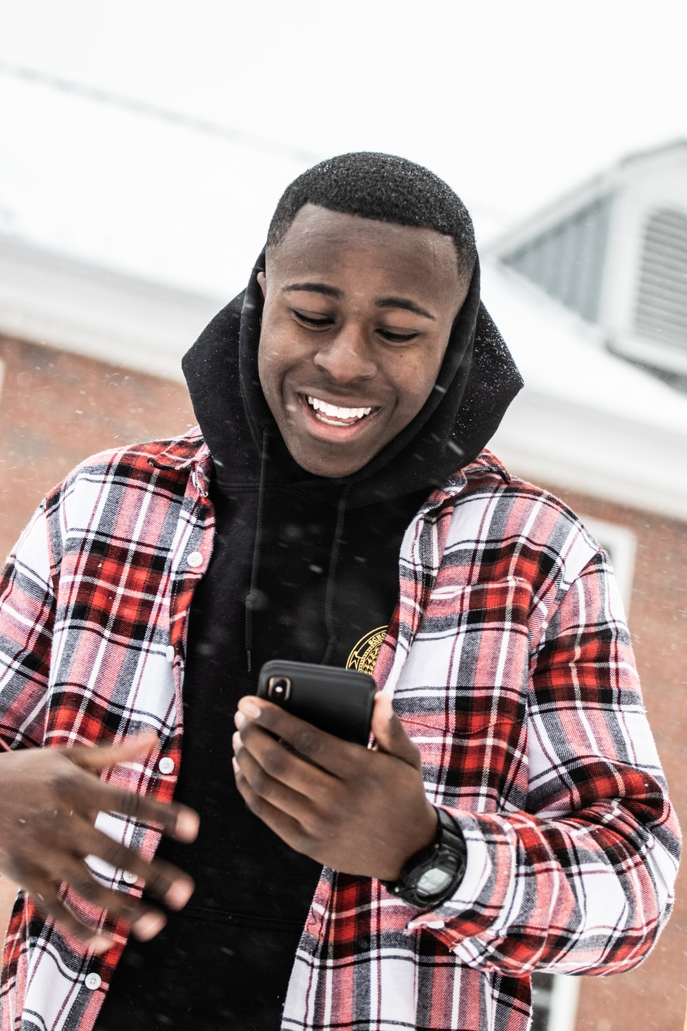 smiling man standing while using phone