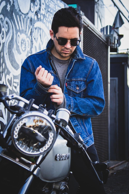 man riding on gray Suzuki motorcycle