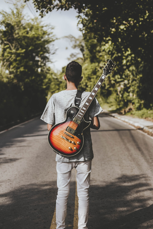 man carrying brown and black Les Paul electric guitar