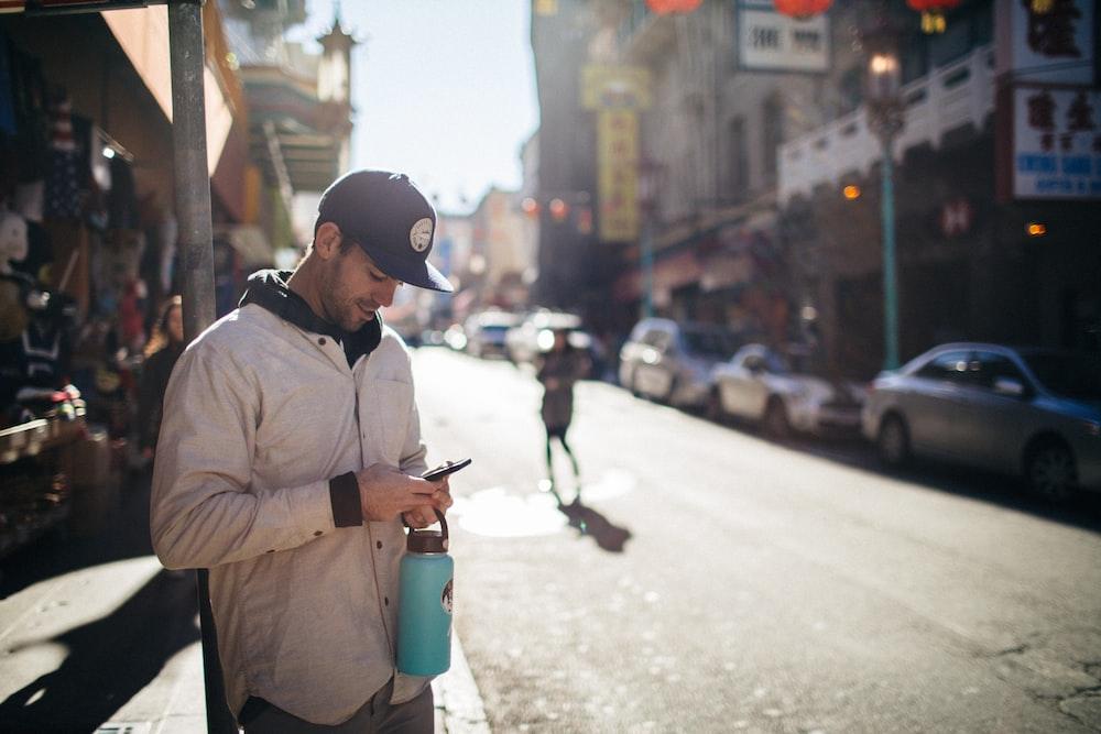 man holding phone beside building