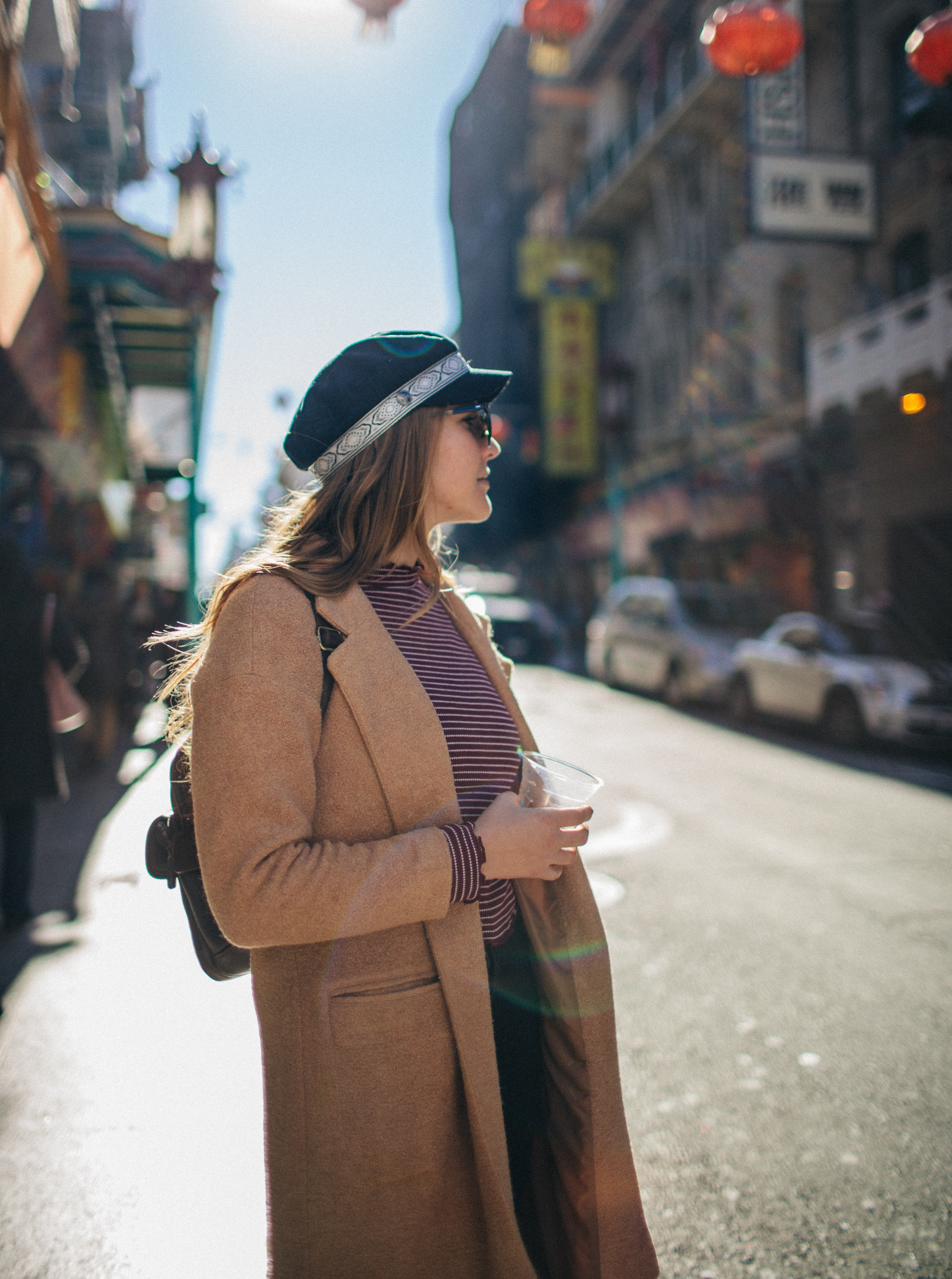 woman in brown coat standing on street during daytime