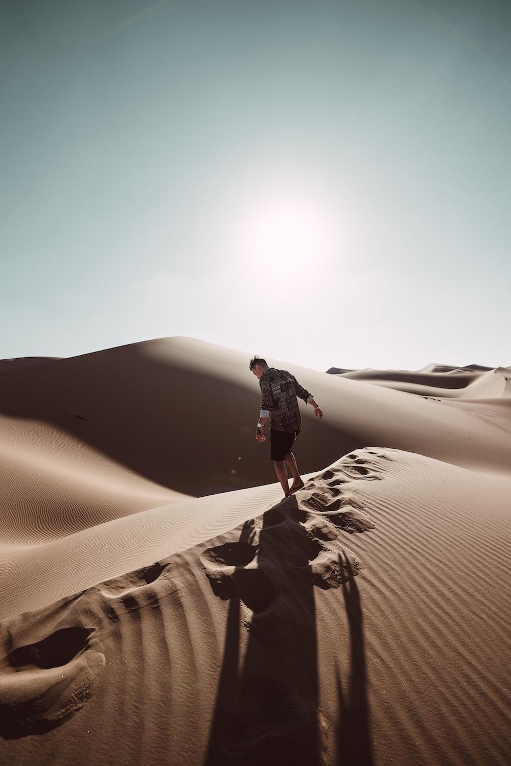 man standing on desert at daytime