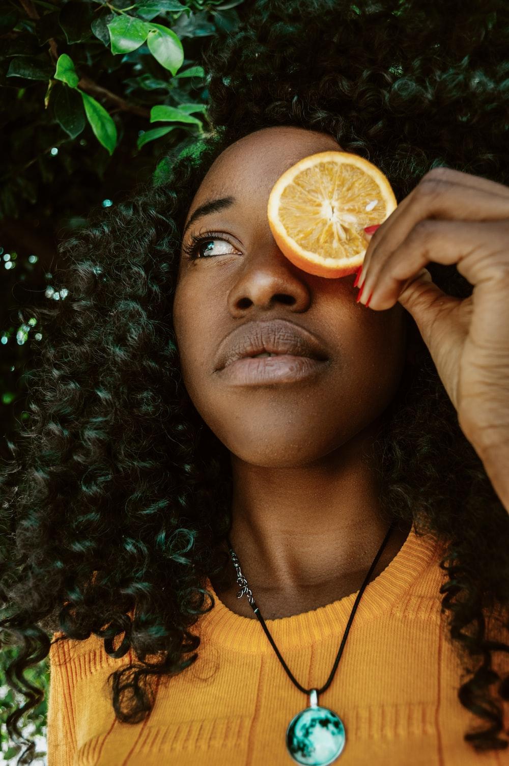 woman putting sliced lime on left eye